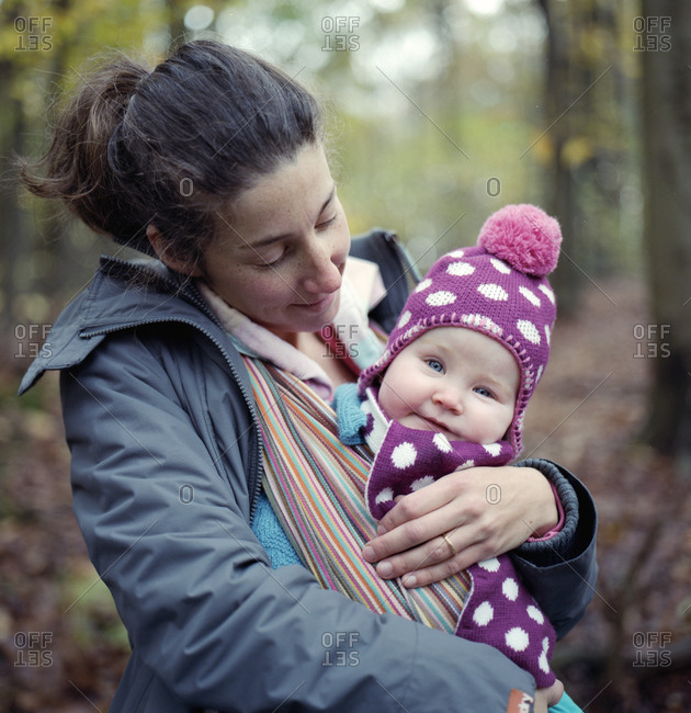 Portrait of a young baby daughter carried by her mother in the woods