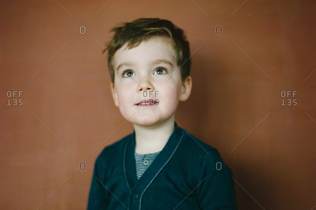 Portrait of a young boy standing in front of a red painted wall