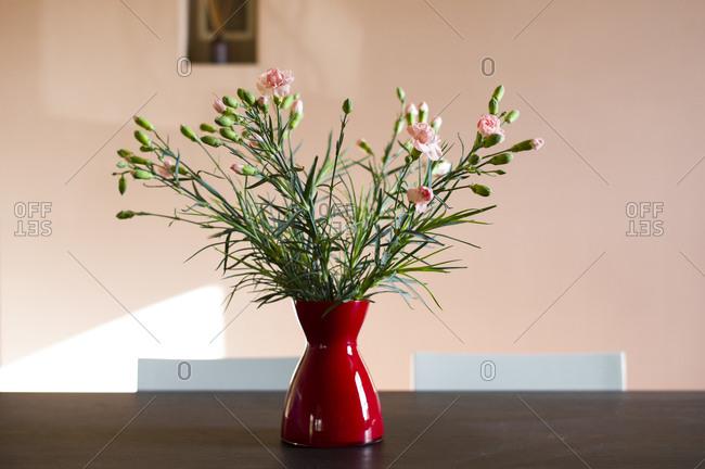Flower vase in warm morning sunlight on table