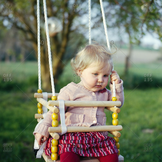 Baby girl on a swing in late afternoon warm light