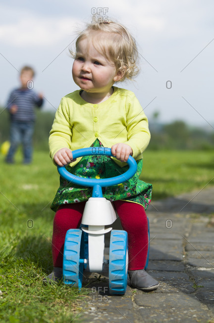 Baby girl riding toy bicycle on path