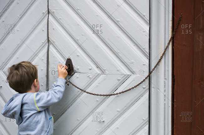 Young boy using a key to open white door of an old wooden church, Sweden