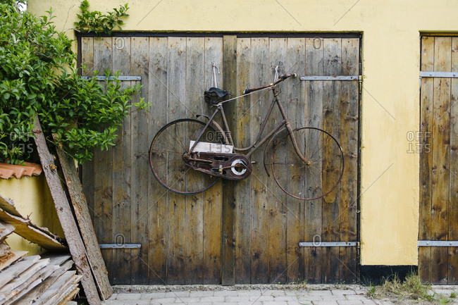 Rusty old bike hanging on a garage door in Denmark