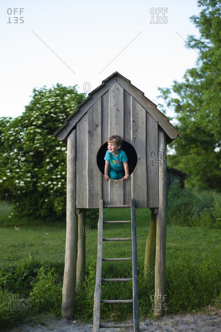Young boy peeking out the doorway of a play house on stilts