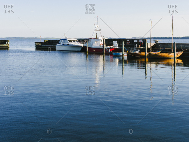 Small fishing boats moored at a dock on a calm sea