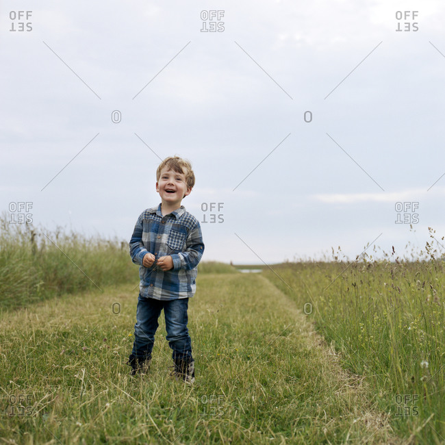 Portrait of a young boy on a walking path on salty meadow on Danish island