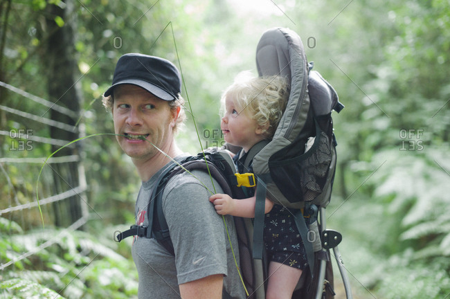 Father and daughter in a carrier bag walking in the woods
