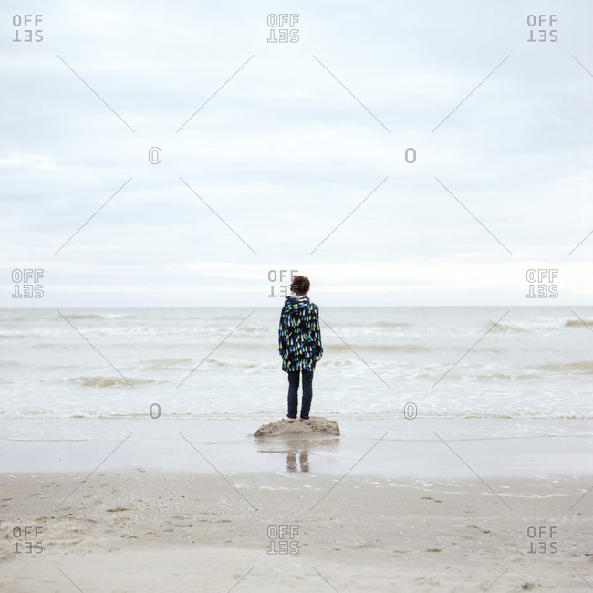 Woman standing on a sandy beach on a gray day looking at the horizon