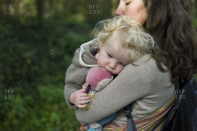 Mother carrying her tired baby daughter on a forest walk
