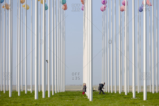Two young siblings running through an art installation by Daniel Buren