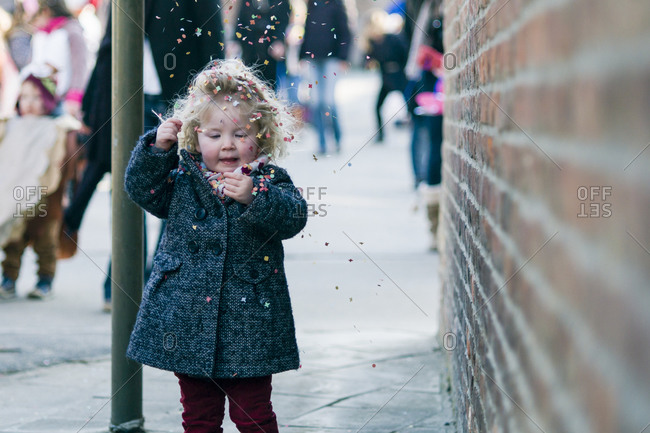 Toddler girl playing with confetti in a small carnival in Belgium