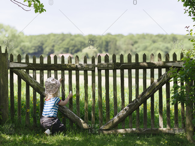 Young girl drawing with chalk on a wooden fence