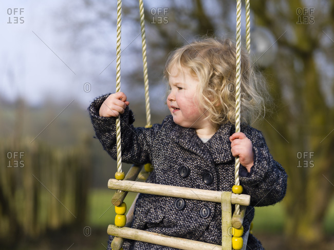 Cute toddler girl riding swing in the garden