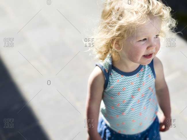 Elevated view of toddler girl standing in sunlight