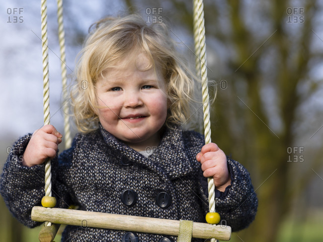 Portrait of an adorable toddler girl riding a swing