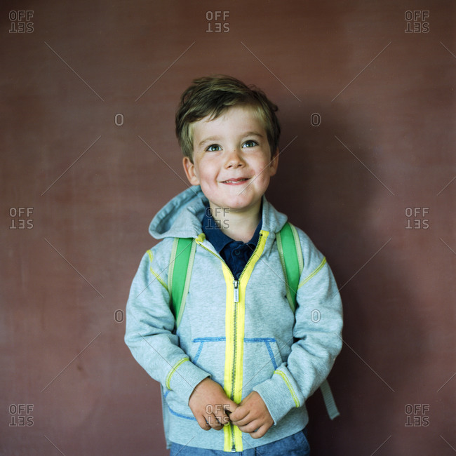Portrait of a young boy with a backpack before school