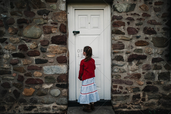 Young girl standing at a locked door on stone building
