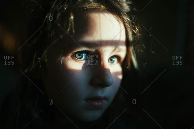 Close-up portrait of a young girl with sunlight on her face
