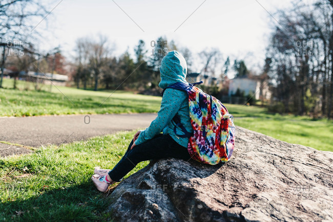 Girl sitting on rock with backpack