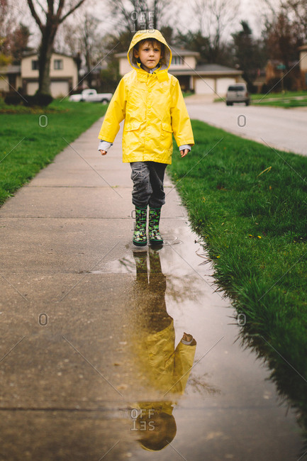 Young boy in a raincoat walking through puddles on a wet sidewalk