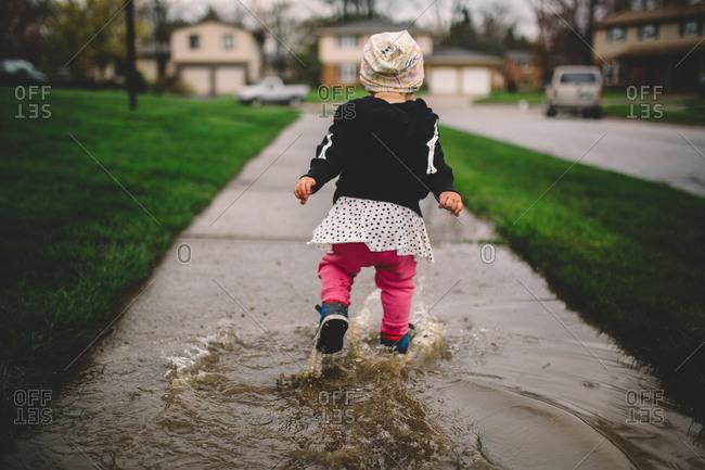 Toddler walking through puddles on a wet sidewalk