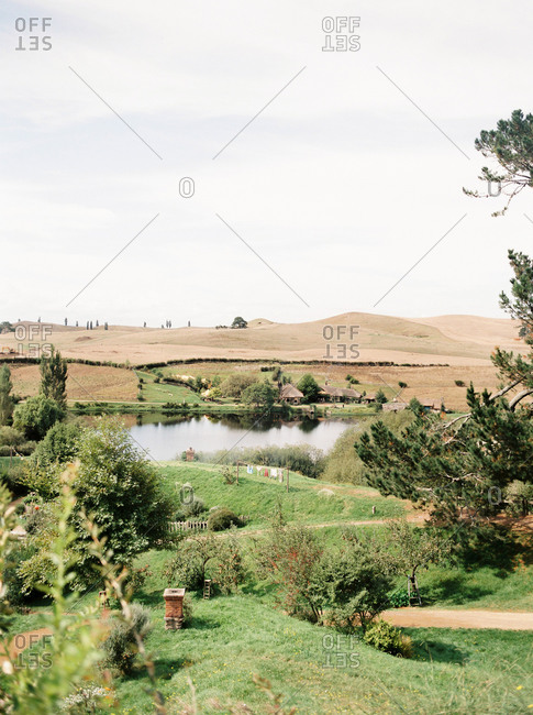 Matamata, New Zealand - April 15, 2015: Scenic view of landscaped movie set with small lake and chimneys