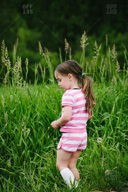 Girl standing in tall grass