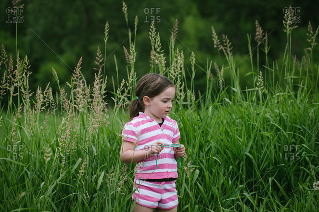 Young girl standing in tall grass