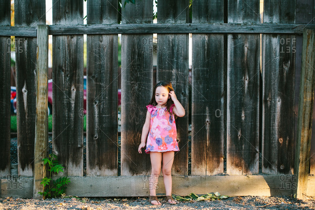 A girl stands in front of a fence brushing her hair behind her ear