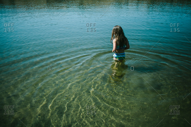 Little girl standing in water of river