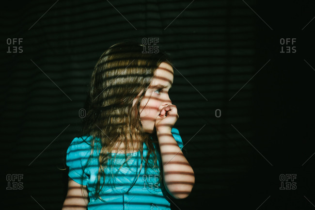 Girl looking to side with shadows from blinds on her