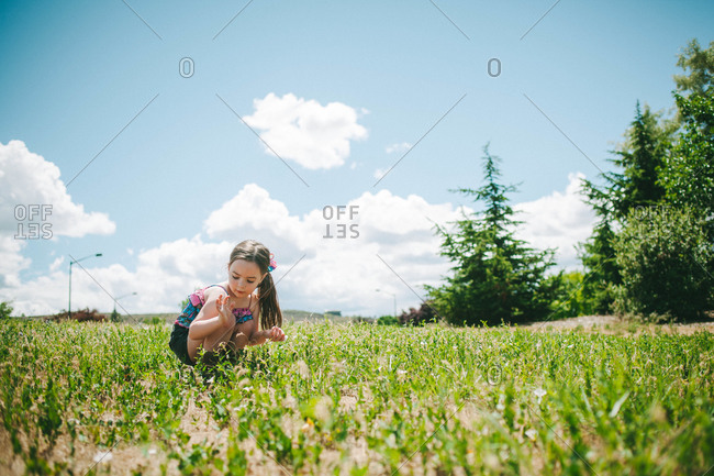 Little girl leaning down to look at flower