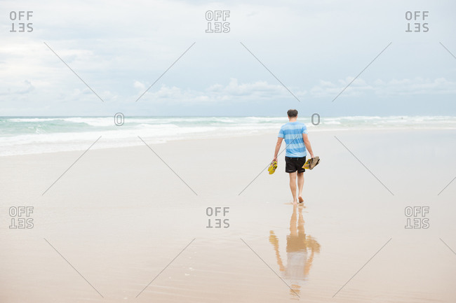 Man carrying sandals on beach