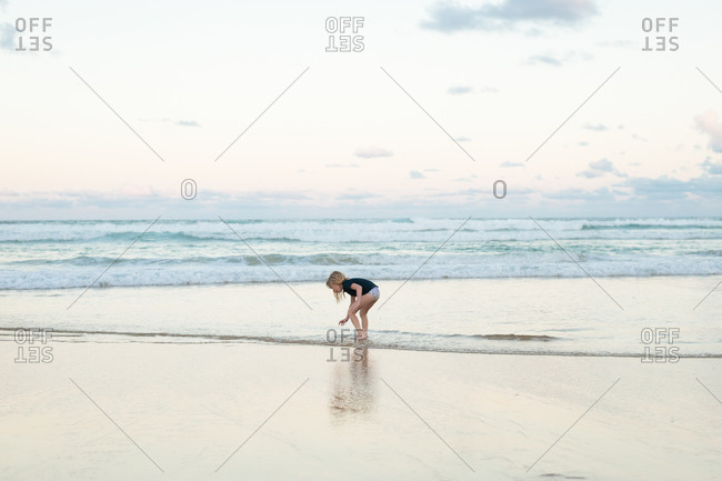 Girl bending over in ocean waves