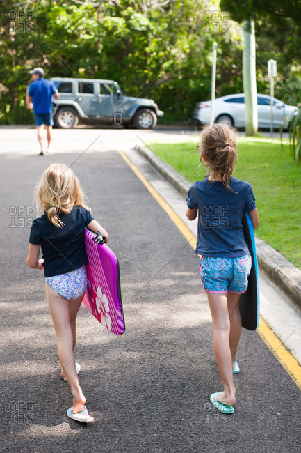 Girls carrying boards for beach
