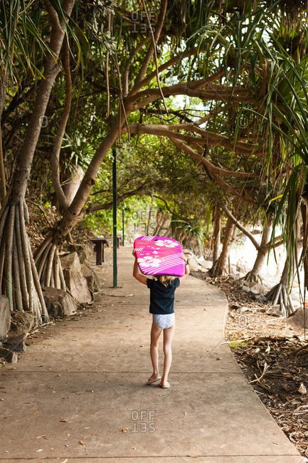 Girl carrying board near ocean