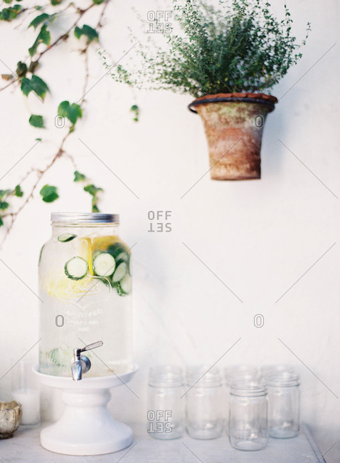 Cucumber and lemon water in a glass dispenser