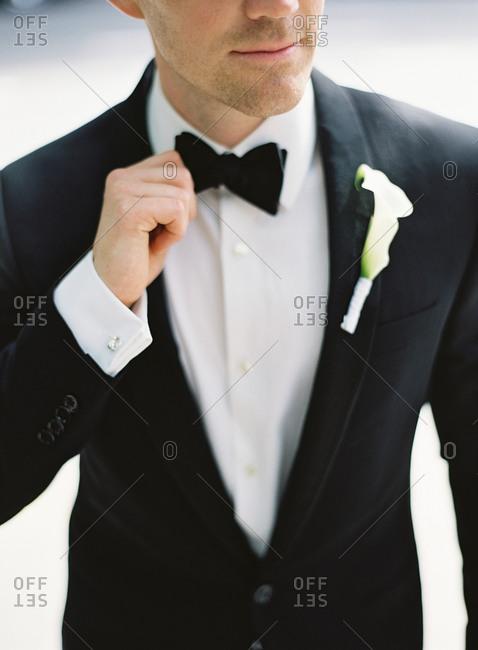 Man putting adjusting his bow tie