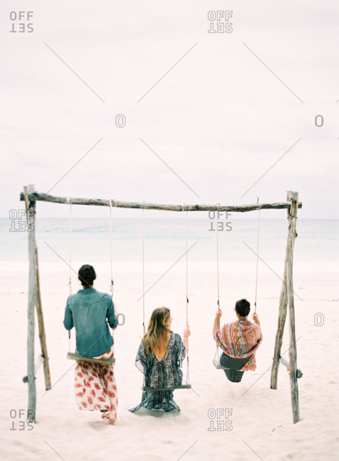Three woman swinging on a beach in Mexico