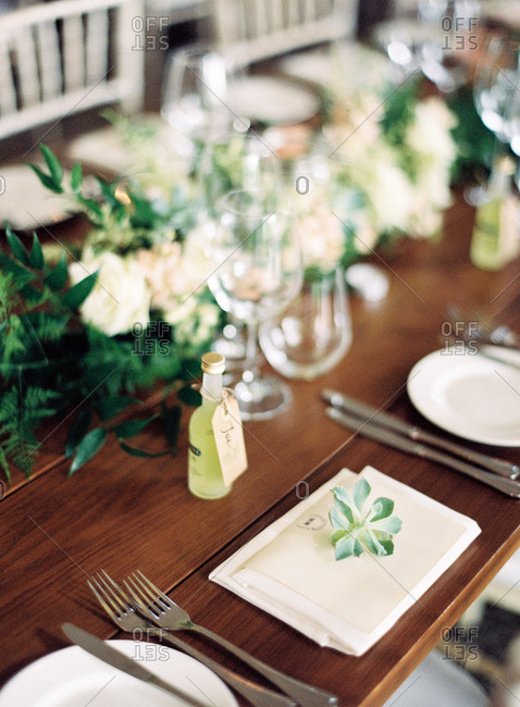 Place setting at a wedding with small bottle of liqueur