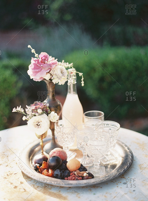 Serving tray with glasses, flowers, fruit and nuts