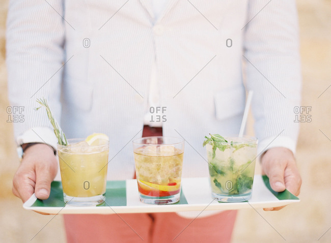 Waiter holding tray with three cocktails