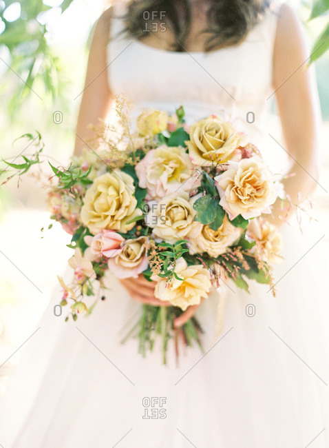Bride holding bouquet with yellow roses