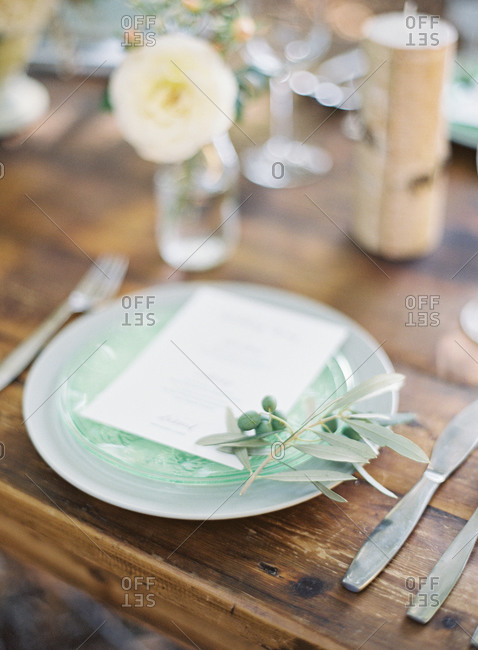 Place setting at a wedding with menu and green berries