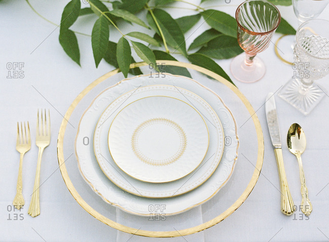 Overhead view of gold and white place setting at a wedding