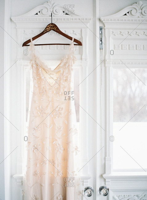 Bridal gown hanging in front of a window