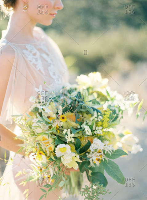 Bride holding bouquet with wildflowers