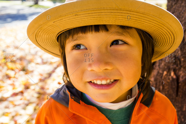 Close up of smiling mixed race boy wearing sun hat