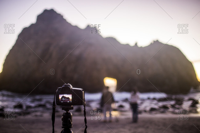 Camera on self-timer taking photograph of couple on beach, Big Sur, California, United States