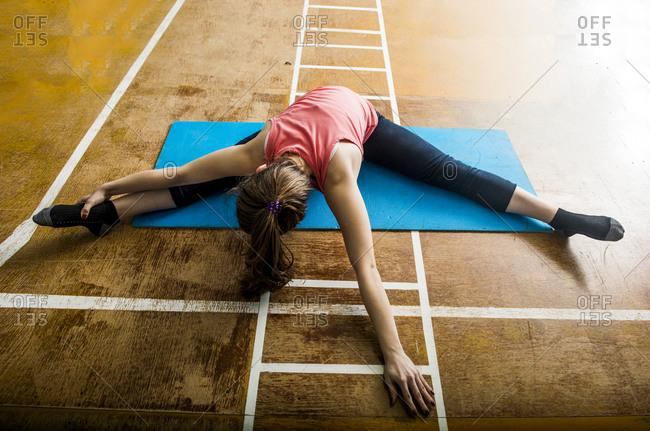 Caucasian dancer stretching in gym